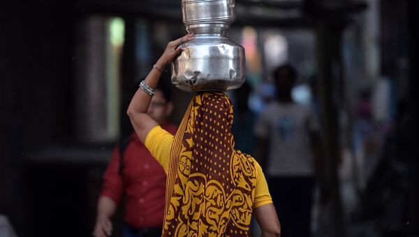An Indian woman carries drinking water containers - Sputnik International
