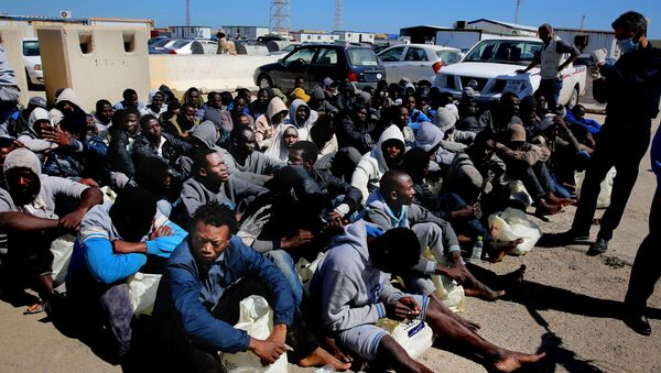 African illegal migrants wait to receive medial assistance after being rescued by coastal guards on a port in Tripoli, Libya. - Sputnik International