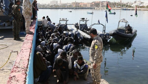 Illegal migrants sit on the dock at the Tripoli port after 115 migrants of African origins were rescued by two coast guard boats at sea when their boat started sinking off the Libyan coast on April 11, 2016 - Sputnik International