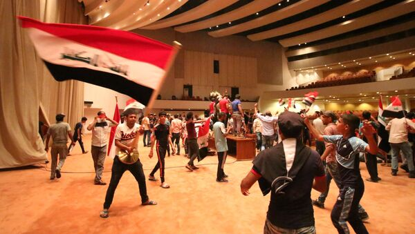 Iraqi protesters wave national flags as they gather inside the parliament after breaking into Baghdad's heavily fortified Green Zone on April 30, 2016 - Sputnik International