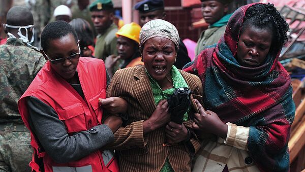 A Kenyan woman (C) mourns the loss of a relative at the site of a building collapse in Nairobi on April 30, 2016. Rescuers in the Kenyan capital made desperate efforts to free survivors including a woman and child trapped in a building that collapsed in storms that have left a total of 17 people dead. - Sputnik International