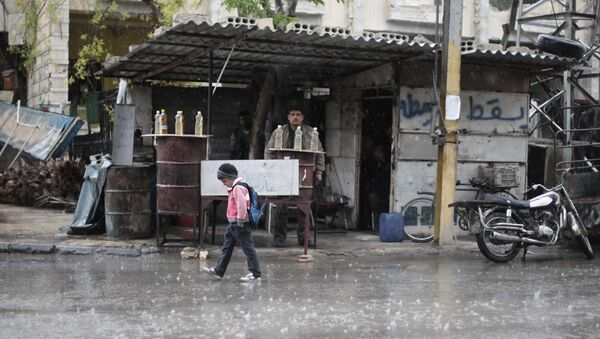 A Syrian schoolboy walks under the rain in Kafr Batna, in the Eastern Ghouta area, on the outskirts of the capital Damascus (File) - Sputnik International