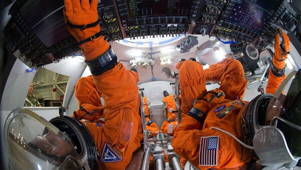 Spacesuit engineers demonstrate how four crew members would be arranged for launch inside the Orion spacecraft, using a mockup of the vehicle at Johnson Space Center. Astronauts will board Orion for a first crewed flight in 2021, and NASA hopes send humans to Mars in Orion in the 2030s  - Sputnik International