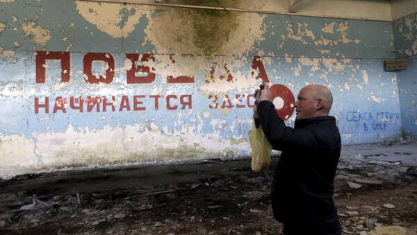 A man takes a picture inside sports hall in the ghost town of a former Soviet military radar station near Skrunda, Latvia, April 9, 2016. The words on the wall reads in Russian Victory starts here - Sputnik International