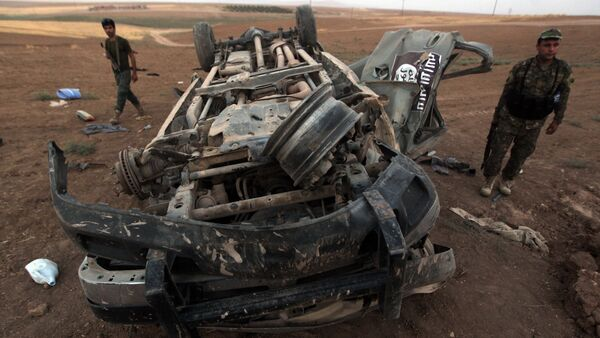 Peshmerga fighters inspect the remains of a car, bearing an image of the trademark jihadist flag, which reportedly belonged to Islamic State (IS) militants after it was targeted by an American air strike in the village of Baqufa, north of Mosul (File) - Sputnik International