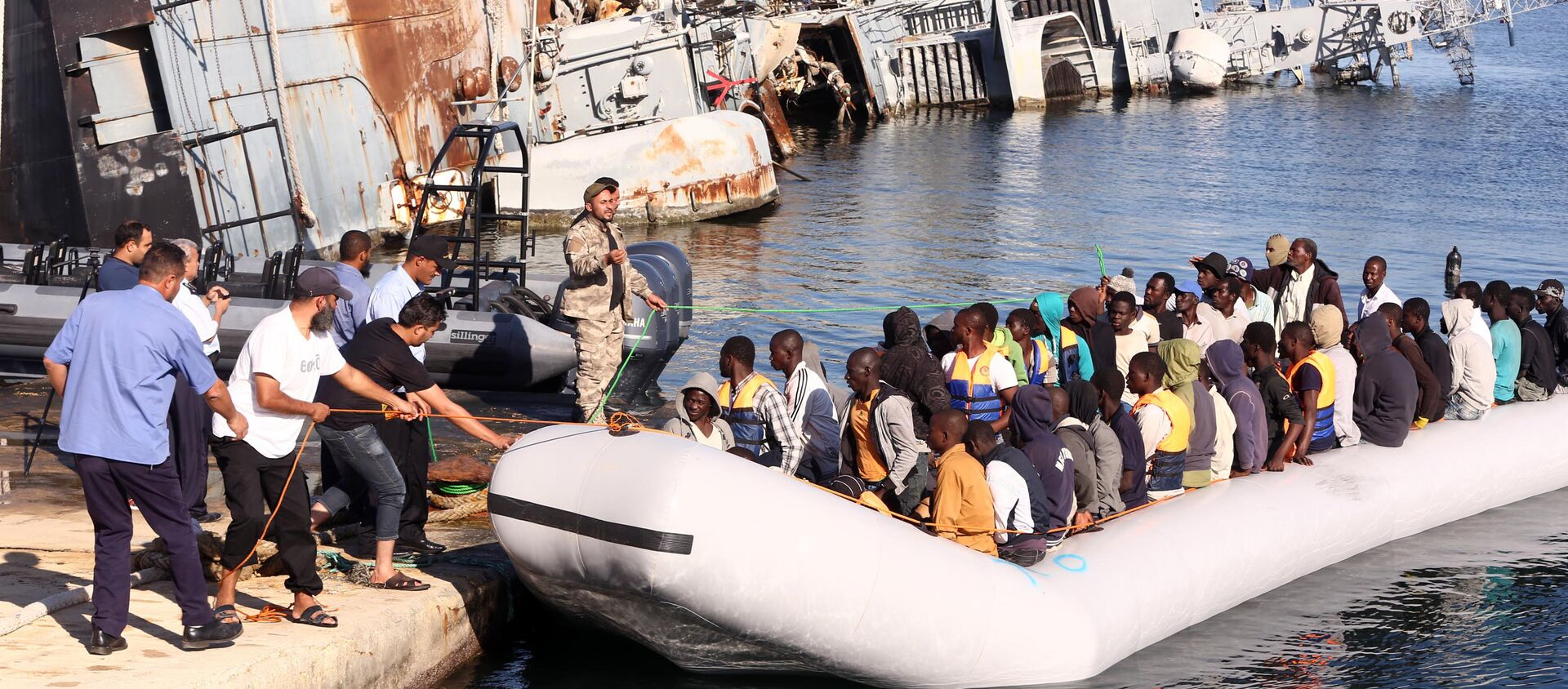 The Libyan coastguard pull a boat carrying illegal African migrants, rescued as they were trying to reach Europe, at a naval base near the capital Tripoli on September 29, 2015.  - Sputnik International, 1920, 24.03.2021