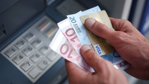 A man takes out Euro banknotes from an automated teller machine (ATM)  - Sputnik International