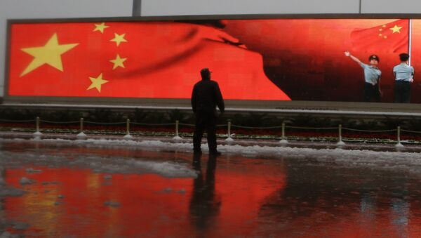 Chinese man stands near a screen displaying the Chinese national flag - Sputnik International