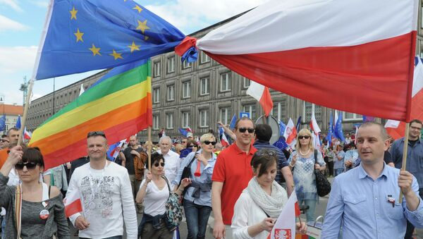 Opponents of Poland's government carry a Polish and EU flags tied together as they march downtown streets to protest the country's direction under a conservative government that is accused of eroding the rule of law, in Warsaw, Poland, Saturday, May 7, 2016. - Sputnik International