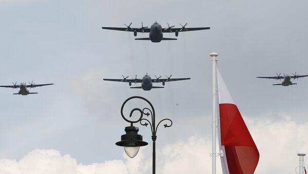 Polish Air Force C-130 Hercules aircraft fly over Poland's national flag during a military parade. - Sputnik International
