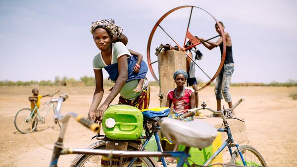 Barry Aliman, 24 years old, bicycles with her baby to fetch water for her family, Sorobouly village near Boromo, Burkina Faso. - Sputnik International