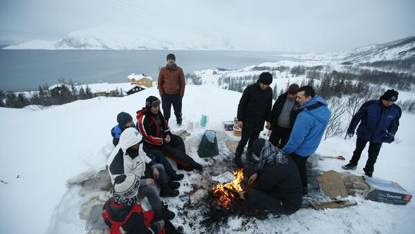 Asylum seekers gather round a fire as they cook a meal overlooking the temporary Altnes camp refugee camp on the island of Seiland, northern Norway (File) - Sputnik International