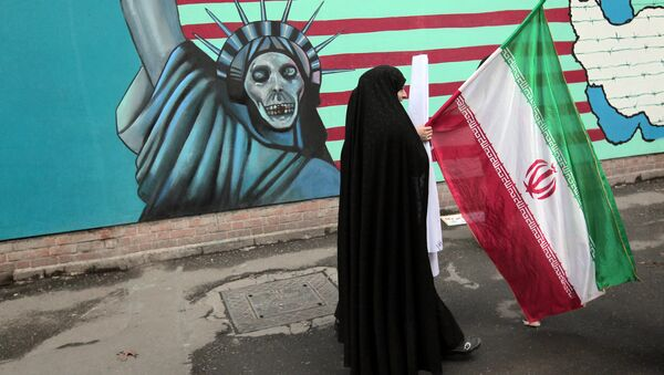 An Iranian woman holds her national flag as she walks past an anti-US mural depicting the Statue of Liberty on the wall of the former US embassy in Tehran (File) - Sputnik International