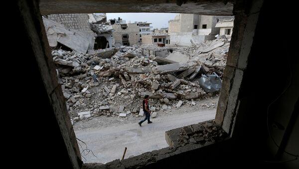 A man walks past damaged buildings in the rebel-controlled area of Maaret al-Numan town in Idlib province, Syria, May 15, 2016 - Sputnik International