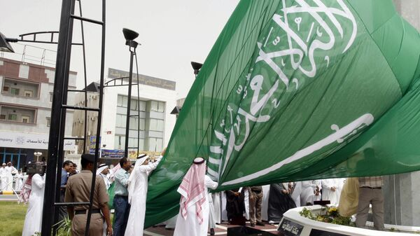 Saudi men unfurl a giant Saudi national flag during a ceremony to raise the highest flag in the country in the eastern city of Dammam on June 17, 2008 - Sputnik International