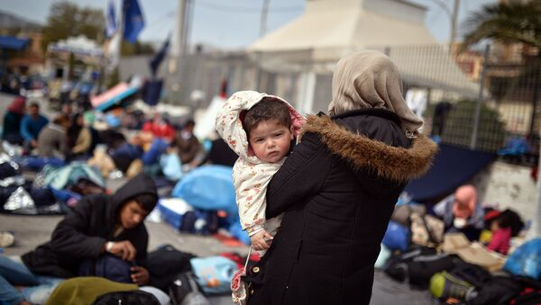 A Syrian woman holds her child at the port of Chios on April 3, 2016 as refugees and migrants who broke out from Chios detention camp, stand in the port of the city. - Sputnik International