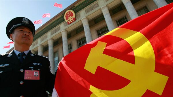 A Chinese policeman holds a Chinese Communist Party flag  - Sputnik International