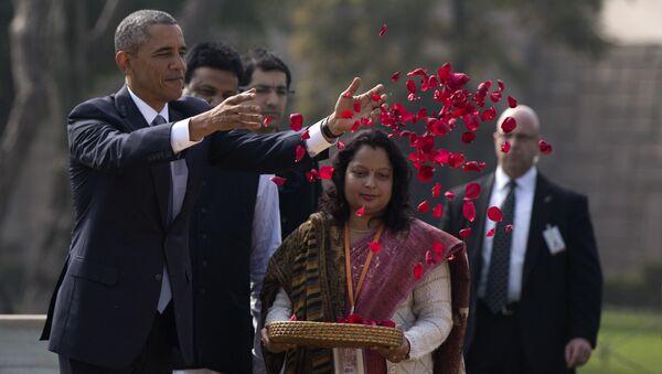 President Barack Obama throws rose petals as he participates in a wreath laying ceremony at the Raj Ghat Mahatma Gandhi Memorial, New Delhi, India, Sunday, Jan. 25, 2015 - Sputnik International
