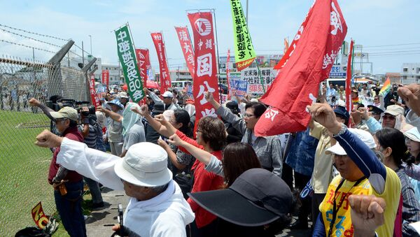 People raise their fists as they shout slogans to protest against the US military presence in front of the US Kadena Air Base in Cyatan, Okinawa prefecture, on May 21, 2016 - Sputnik International