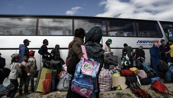Refugees stand near a bus as they wait to be transferred to a hospitality centre during a police operation at a refugee camp at the border between Greece and Former Yugoslav Republic of Macedonia (FYROM), near the village of Idomeni, northern Greece,on May 25, 2016 - Sputnik International