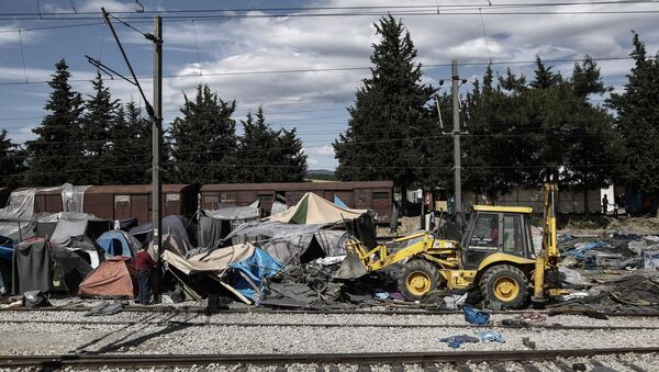 A bulldozer clears the debris at the site of the makeshift refugee and migrant camp in Idomeni close to the Greek-Macedonian border on May 25, 2016 - Sputnik International