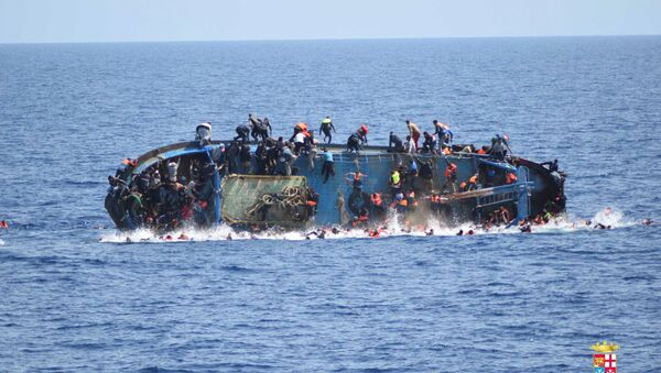 Migrants are seen on a capsizing boat before a rescue operation by Italian navy ships Bettica and Bergamini off the coast of Libya in this handout picture released by the Italian Marina Militare on May 25, 2016 - Sputnik International