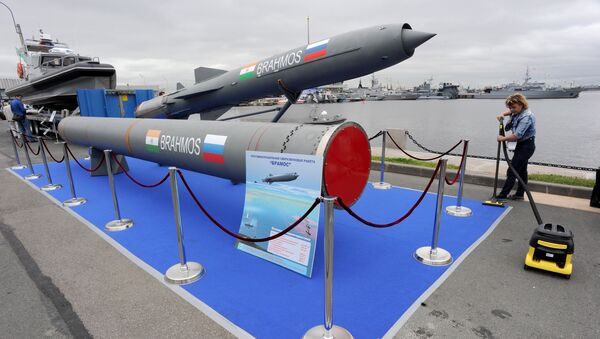 A woman cleans a carpet flooring close to a Brahmos supersonic cruise missile at the International Maritime Defence Show in St. Petersburg on July 2, 2015. - Sputnik International