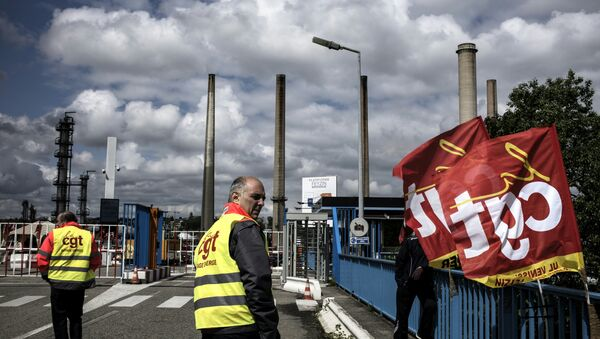 A worker stands next to French CGT union flags in front of the Total oil refinery of Feyzin, near Lyon, central-eastern France, on May 24, 2016, during a strike at the plant to protest against government labour reforms - Sputnik International