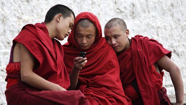 Buddhist monks looking at a mobile phone - Sputnik International