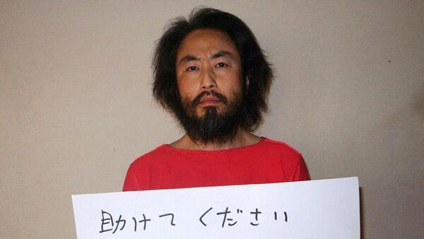 This undated picture provided by Japan's Jiji Press news agency, taken at an undisclosed location, on May 30, 2016 shows Japanese freelance journalist Jumpei Yasuda holding a piece of paper with a handwritten message in Japanese. The fresh photo, which received widespread coverage in Japanese media on May 30, 2016, shows Yasuda, who has been missing for almost a year, wearing an orange shirt, his hair and beard grown long. - Sputnik International