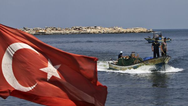 A Turkish flag hangs in the Gaza port as fishermen in their boats pass off the shore of Gaza City, Tuesday, Sept. 13, 2011 - Sputnik International