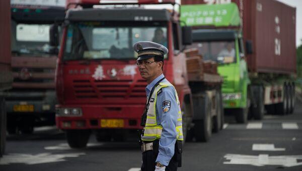 Policeman gestures in front of trucks, China - Sputnik International