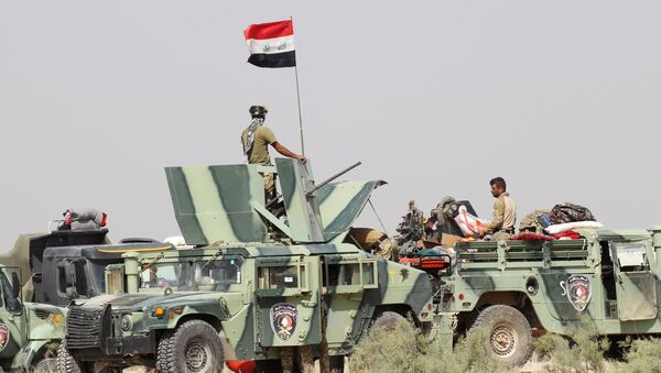 Iraqi security forces sit in military vehicles in suburb of Fallujah, Iraq - Sputnik International