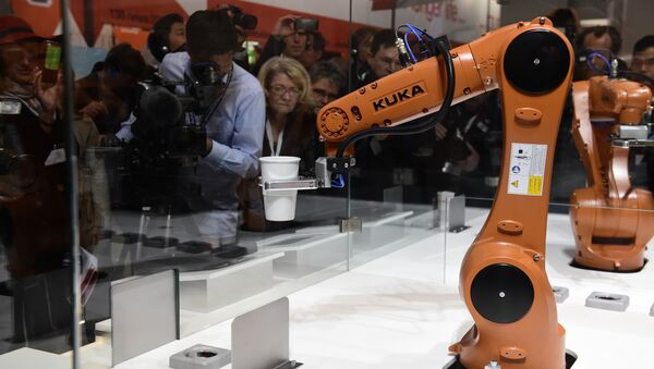 A robot prepares a cup of coffee at the booth of robotics manufacturer KUKA on the eve of the opening of the Hannover Messe (Hanover fair) in Hanover, northern Germany, on April 23, 2016 - Sputnik International