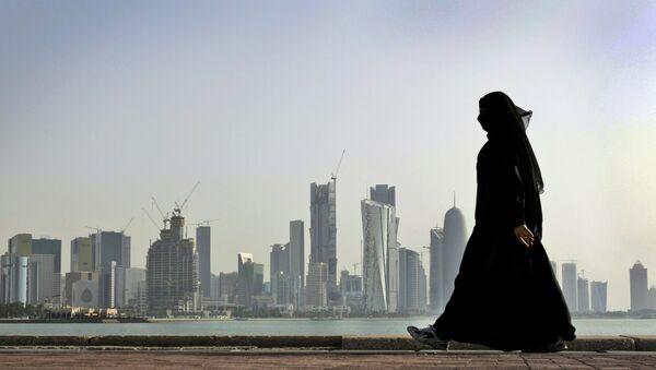A Qatari woman walks in front of the city skyline in Doha, Qatar. - Sputnik International