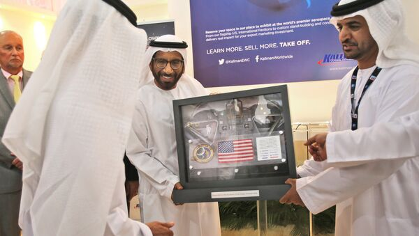 Khalifa Mohammed Al Rumaithi, Chairman of the UAE Space Agency, center, receives a United States of America flag and other memorabilia from the 1971 Apollo 14 lunar mission from Kallman Worldwide during the third day of the Dubai Airshow in the United Arab Emirates, Tuesday, Nov. 10, 2015. - Sputnik International