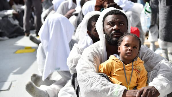 A man and his daughter wait during a distribution of meals aboard the rescue ship Aquarius, on May 25, 2016 a day after a rescue operation of migrants and refugees off the Libyan coast. - Sputnik International