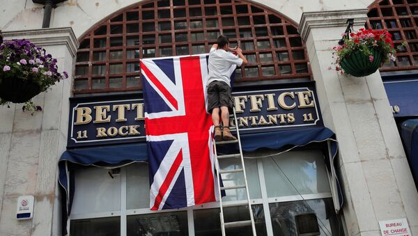 A worker places the Union Jack flag on the facade of a shop at Casesmates square where British Prime Minister David Cameron will attend a 'Stronger In' campaign event in the British overseas territory Gibraltar, historically claimed by Spain, June 16, 2016. - Sputnik International