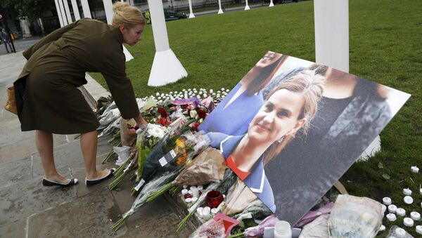 A woman leaves a floral tribute next to a photograph of murdered Labour Member of Parliament Jo Cox in Parliament Square, London, Britain June 17, 2016 - Sputnik International