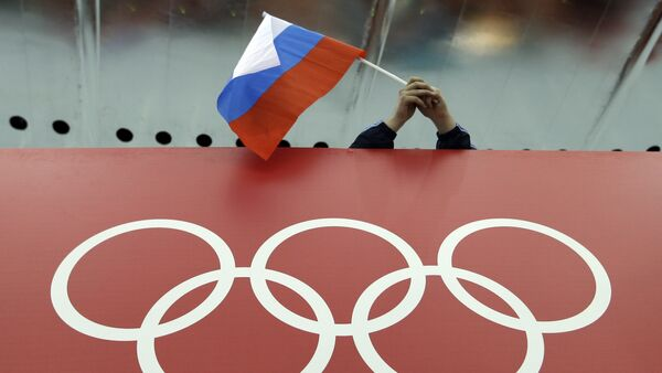 In this Feb. 18, 2014 file photo, a Russian skating fan holds the country's national flag over the Olympic rings before the start of the men's 10,000-meter speedskating race at Adler Arena Skating Center during the 2014 Winter Olympics in Sochi, Russia - Sputnik International