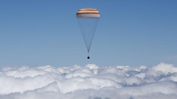 The Soyuz TMA-19M capsule carrying International Space Station (ISS) crew members, Tim Peake of Britain, Yuri Malenchenko of Russia and Tim Kopra of the U.S., descends beneath a parachute just before landing near the town of Zhezkazgan, Kazakhstan, on June 18, 2016 - Sputnik International
