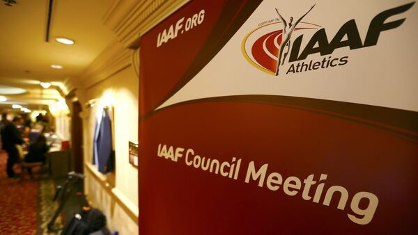 Journalists are seen near a logo of the International Association of Athletics Federations (IAAF) at a hotel where the IAAF council holds a meeting in Vienna, Austria, June 17, 2016 - Sputnik International
