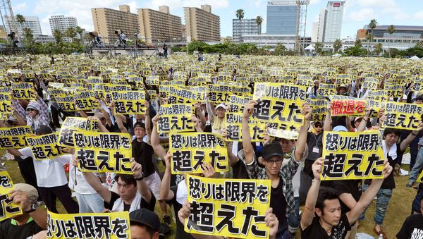 Protesters raise placards reading Anger was over the limit during a rally against the U.S. military presence on the island and a series of crimes and other incidents involving U.S. soldiers and base workers, at a park in the prefectural capital Naha on Japan's southern island of Okinawa, Japan, in this photo taken by Kyodo June 19, 2016 - Sputnik International