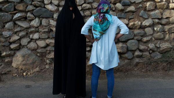 Today in the streets of Tehran and other large Iranian cities (Isfaghan, Shiraz, Tebriz) often women are seen wearing two types of hijabs: Chador (left) and Manto (loose colorful body cover) with Rosari (light headscarf with colorful flowers). First option is more conservative, second is modern and popular with the younger generation. - Sputnik International