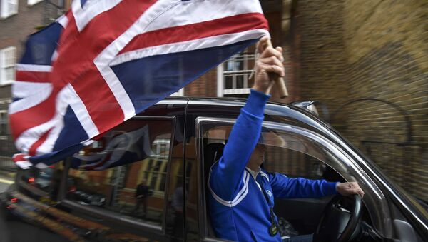A taxi driver holds a Union flag, as he celebrates following the result of the EU referendum, in central London, Britain June 24, 2016. - Sputnik International