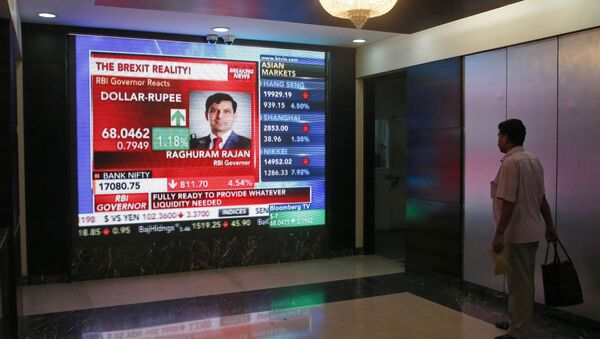 A man watches Reserve Bank of India governor Raghuram Rajan commenting on the situation after stock markets tumbled worldwide, on a stock markets indicator board in Mumbai, India, Friday, June 24, 2016. - Sputnik International