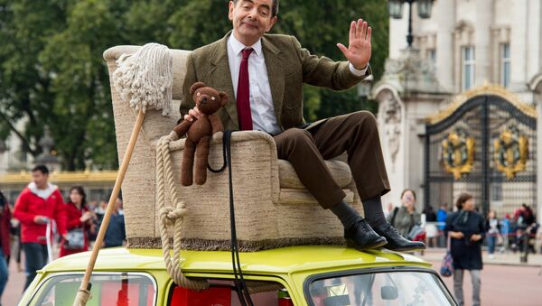 British actor Rowan Atkinson, dressed as Mr Bean, sits on top of a Mini Cooper outside Buckingham Palace, London, to promote the 25th anniversary of Mr Bean, London, Friday, Sept. 4, 2015. - Sputnik International