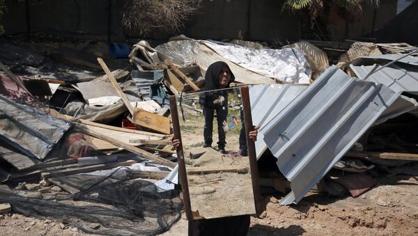 A woman from the Arab Jahalin Bedouin community carries a mirror after the demolition of her home in the West Bank Bedouin camp of al-Khan al-Ahmar on April 7, 2016 - Sputnik International