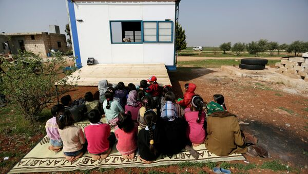 Children watch as volunteer teachers perform a puppet show inside a mobile educational caravan for children who do not have access to schools on the outskirts of the Syrian rebel-held town of Saraqib, Idlib province March 10, 2016 - Sputnik International