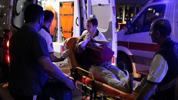 An injured woman covers her face as she is carried by paramedics into ambulance at Istanbul Ataturk airport, Turkey, following a blast June 28, 2016. - Sputnik International